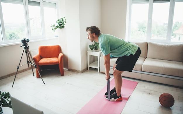 Kaukasische fitnesstrainer die rekoefeningen doet voor camera met een elastische band die sportkleding draagt