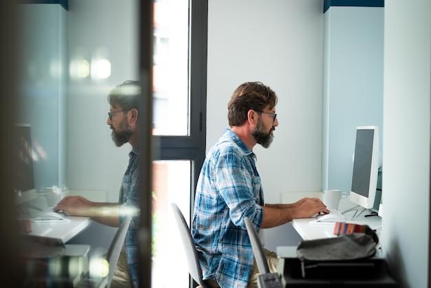 Kaukasische freelance mensen man zit aan het bureau te typen op desktopcomputer voor online baan internet verbonden levensstijl - hipster volwassen man die thuis of op kantoor werkt cowork ruimte alleen