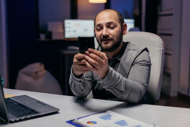 Kaukasische freelancer-berichten in de loop van de avond aan het bureau. zakenman die zijn cel gebruikt om een sms te sturen terwijl hij 's avonds laat op kantoor werkt om een deadline te halen.