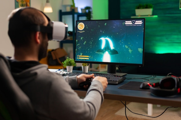 Kaukasische gamer die space shooter-kampioenschap speelt terwijl hij een virtual reality-headset draagt. verslagen gamer met professionele console voor online toernooi 's avonds laat in de gameroom