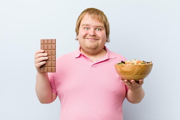 Kaukasische gekke blonde dikke man die kiest tussen chocoladetablet of slakom