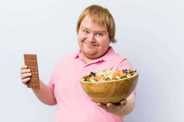 Kaukasische gekke blonde dikke man die tussen chocoladetablet of slakom kiest