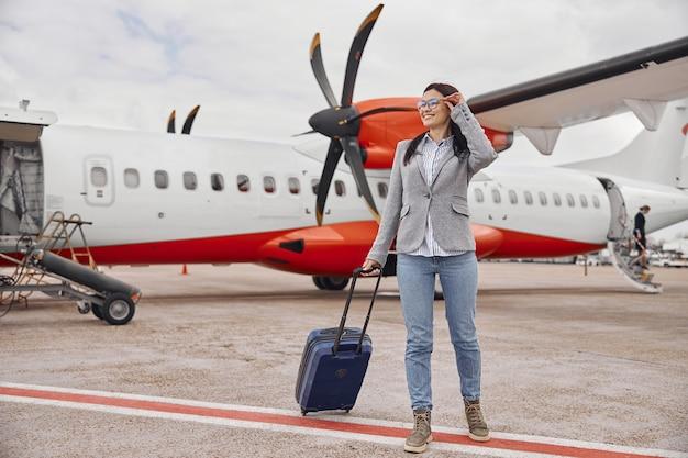 Kaukasische gelukkige vrouw lacht in de buurt van het vliegtuig voordat ze aan boord gaat