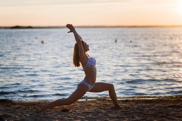 Kaukasische geschikte vrouw met sportlichaam stellen op strand in zonsondergangtijd. gewichtsverlies in de zomer, motivatie.