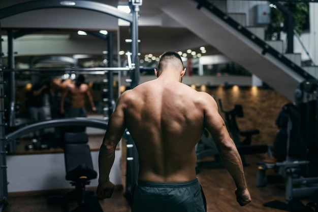 Kaukasische gespierde shirtless man poseren in de sportschool