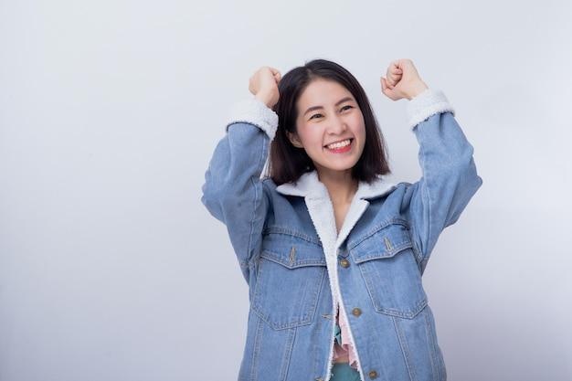 Kaukasische glimlachende opgewekte vrouw die haar hand met uitdrukking toont die verrast en verbaasd voelen, positief aziatisch meisje die blauwe vrijetijdskleding dragen