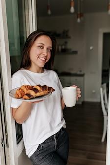 Kaukasische glimlachende vrouw die wit t-shirt met donker haar en een gezonde huid draagt die ochtendkoffie en croissants voor ontbijt thuis houdt.
