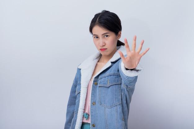 Kaukasische glimlachende vrouwen die handeinde, slecht emotie jong aziatisch meisje tonen die blauw vrijetijdskledingsportret dragen