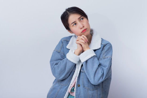 Kaukasische glimlachende vrouwen die, slecht emotie jong aziatisch meisje denken die blauw vrijetijdskledingsportret dragen