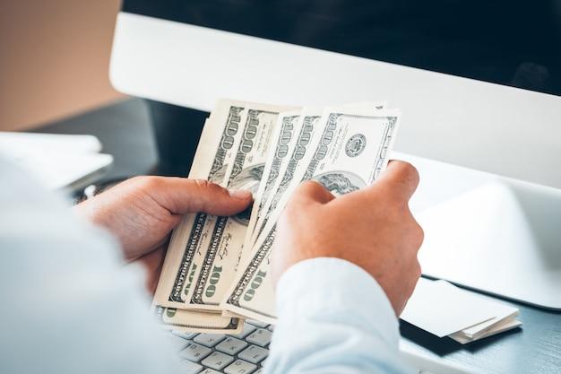 Kaukasische handen die dollarbankbiljetten tellen