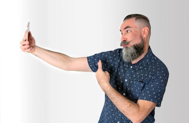 Kaukasische hipster met grijze baard die overwinningsteken naar zijn smartphone doet.