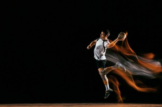 Kaukasische jonge handbalspeler in actie en beweging in gemengde lichten over zwarte studio achtergrond. fit mannelijke professionele sportman. concept van sport, beweging, energie, dynamische, gezonde levensstijl.