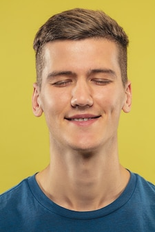 Kaukasische jonge man close-up op gele studio
