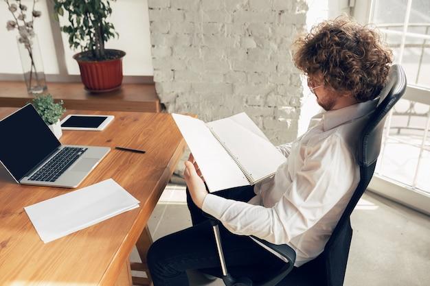 Kaukasische jonge man in zakelijke kleding werkzaam in kantoorbaan online studeren