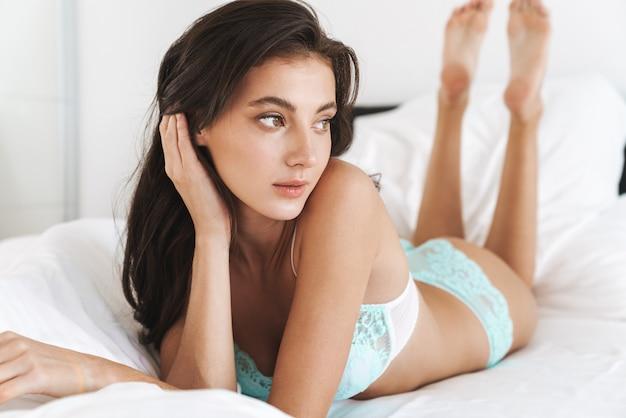 Kaukasische jonge mooie vrouw die kantenlingerie draagt die op wit bedlinnen thuis ligt