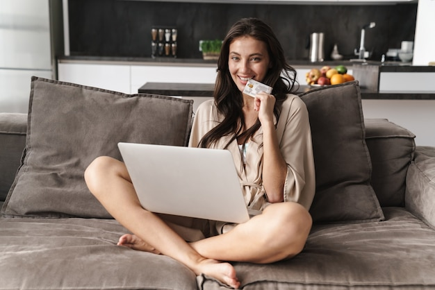 Kaukasische jonge mooie vrouw in vrijetijdskleding die laptop en creditcard op bank thuis met behulp van