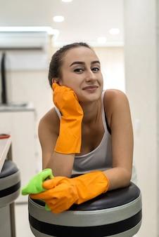 Kaukasische jonge vrouw die met detergentia haar nieuwe keukenruimte schoonmaakt