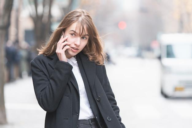Kaukasische jonge vrouw die met iemand met smartphone op oor spreekt