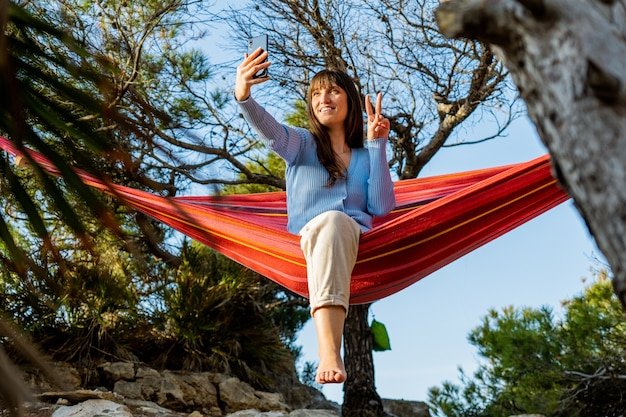 Kaukasische jonge vrouw die selfie in hangmat neemt bij zonsondergang