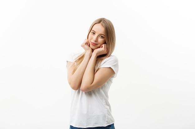 Kaukasische jonge vrouw met schattige schattige speelse verlegen glimlach. model wit t-shirt geïsoleerd op een witte achtergrond.