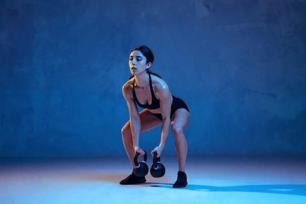Kaukasische jonge vrouwelijke atleet die op blauw in neonlicht oefent