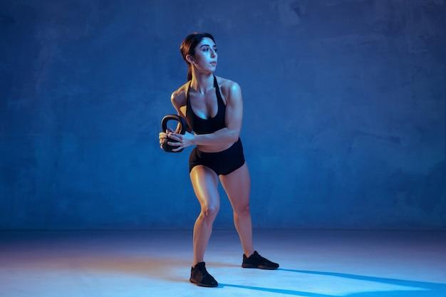 Kaukasische jonge vrouwelijke atleet die op blauw oefent