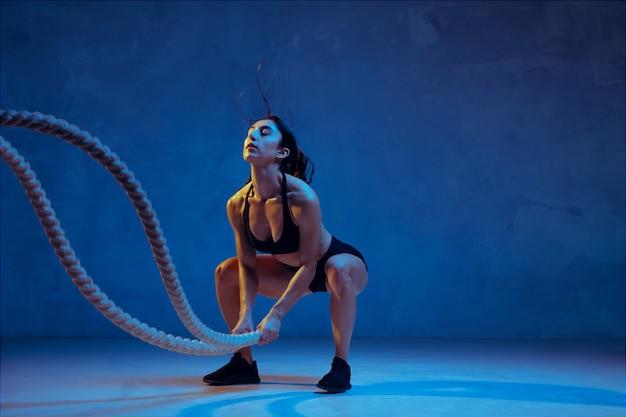 Kaukasische jonge vrouwelijke atleet oefenen op blauwe studio achtergrond in neonlicht. sportief model traint haar bovenlichaam met touwen. body building, gezonde levensstijl, schoonheid en actie concept.