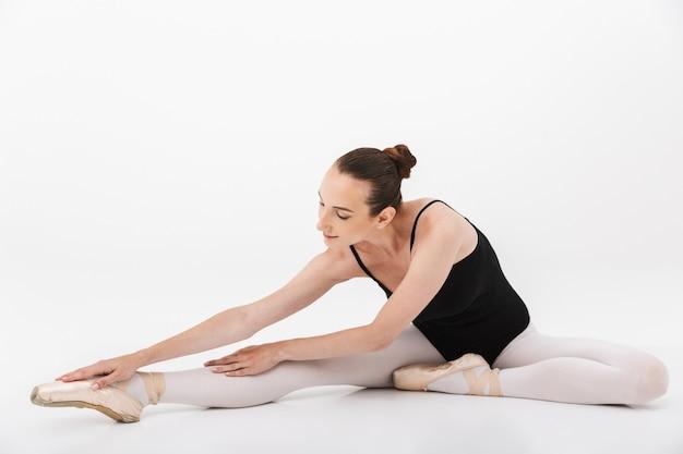 Kaukasische jonge vrouwenballerina die en haar lichaam oefent en uitrekt dat over witte muurachtergrond wordt geïsoleerd