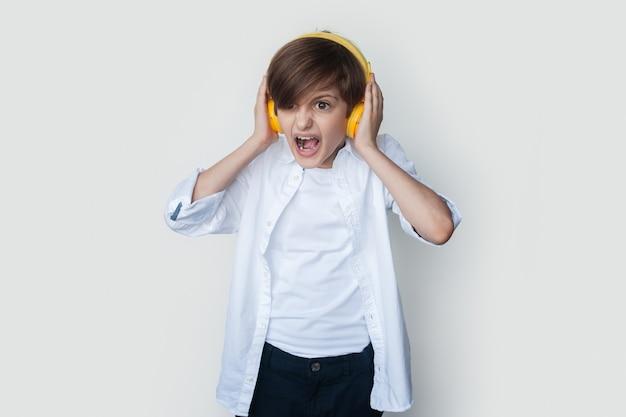 Kaukasische jongen die op een witte studiomuur schreeuwt terwijl hij naar te luide muziek luistert met een hoofdtelefoon