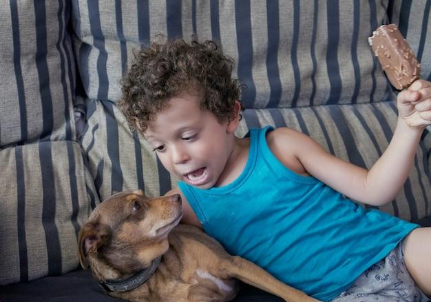 Kaukasische jongen met krullend haar liggend met zijn puppy op de bank en een ijsje in zijn hand