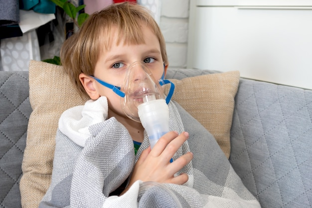 Kaukasische jongetje inademing met vernevelaar thuis maken. het kind houdt een inhalator van de maskerdamp vast.