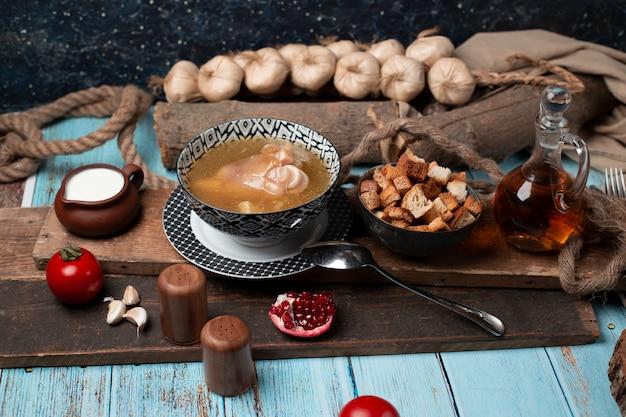Kaukasische khash in kom met yoghurt, crackers en tomaten