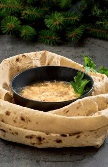 Kaukasische khash-soep in een kom, met lavashtaarten en kruiden, close-up. traditioneel armeens of turks gerecht is soep, geserveerd met verse groenten, knoflook en gedroogd knapperig lavashbrood.