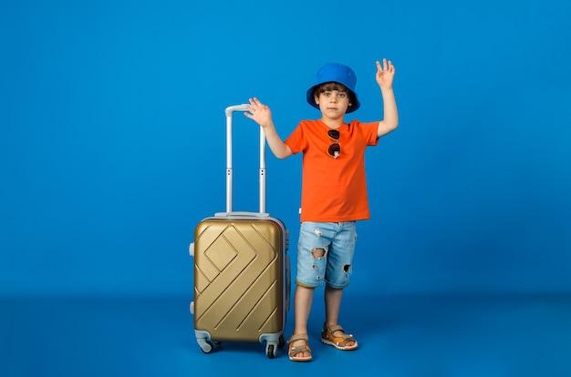 Kaukasische kleine jongensreiziger in panama houdt een gele koffer op een blauwe ondergrond met ruimte voor tekst