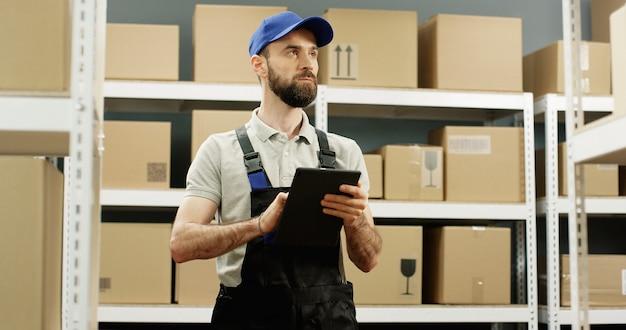 Kaukasische knappe jonge postbode die zich in postopslag met pakketten bevindt en op tabletcomputer tikt.