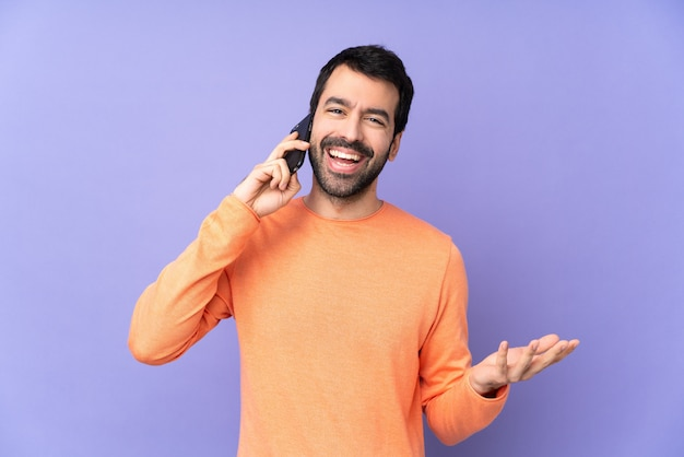 Kaukasische knappe man over geïsoleerde paars houden een gesprek met de mobiele telefoon met iemand