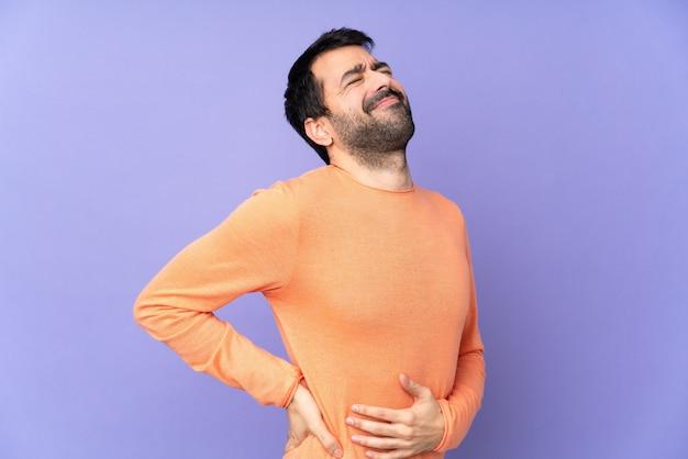 Kaukasische knappe man over paarse muur die lijden aan rugpijn