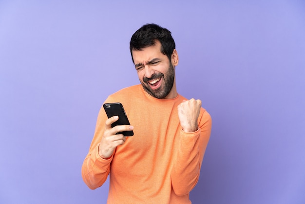Kaukasische knappe man over paarse muur met telefoon in overwinningspositie