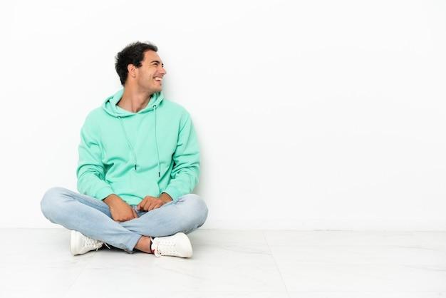 Kaukasische knappe man zittend op de vloer lachend in zijpositie