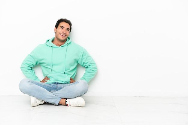 Kaukasische knappe man zittend op de vloer poseren met armen op heup en glimlachend