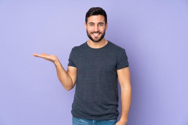 Kaukasische knappe mens die denkbeeldig op de palm houdt om een geïsoleerde advertentie in te voegen