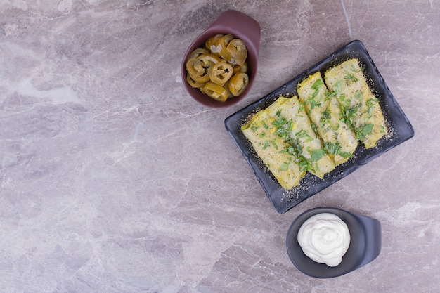 Kaukasische koolwraps met vullingen in een zwarte schotel met yoghurt en gemarineerde groenten