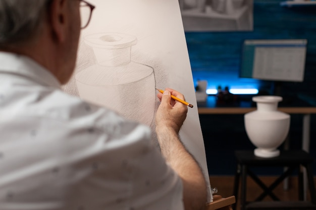 Kaukasische kunstenaar die vaas op bureau bekijkt en op canvas trekt