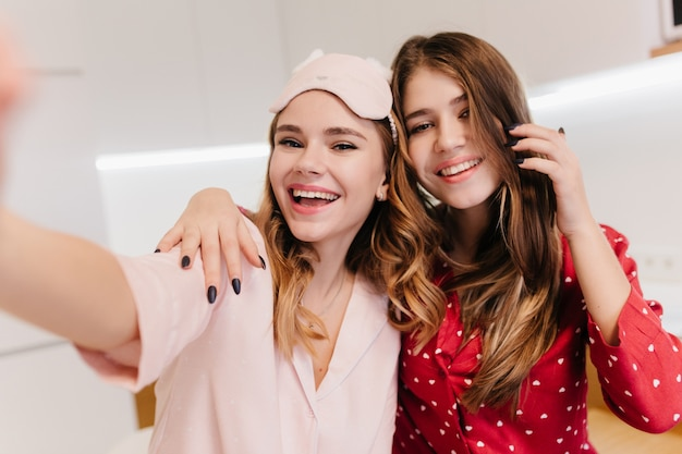 Kaukasische lachende dame selfie met vriend maken in goedeweekendochtend. verfijnd meisje met lang kapsel dat plezier heeft met schattige zus. Gratis Foto
