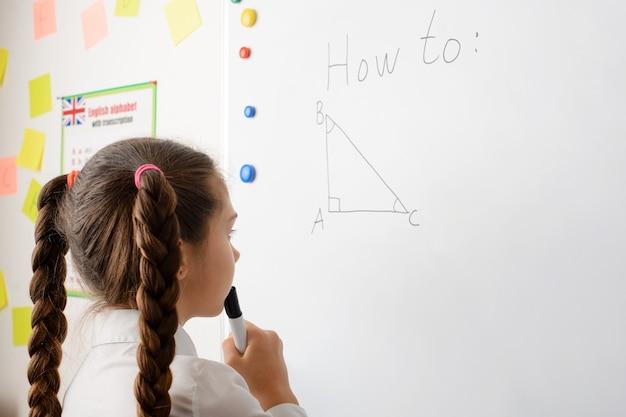 Kaukasische leerling van het secundair onderwijs die geometrische taak op het bord uitvoert, denkend aan de stelling van pythagoras