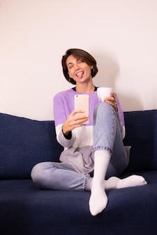 Kaukasische leuke vrouw blogger thuis in warme paarse trui pullover selfie in spiegel op mobiele telefoon