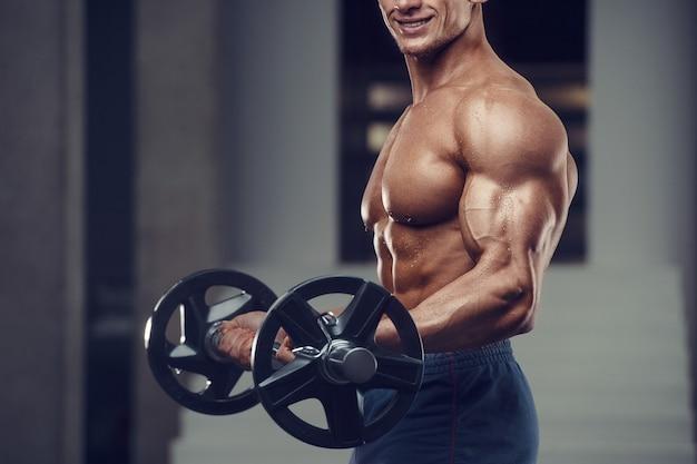 Kaukasische macht atletische man training oppompen van biceps spieren. sterke bodybuilder met sixpack, perfecte buikspieren, triceps, borst, schouders in de sportschool. fitness en bodybuilding concept