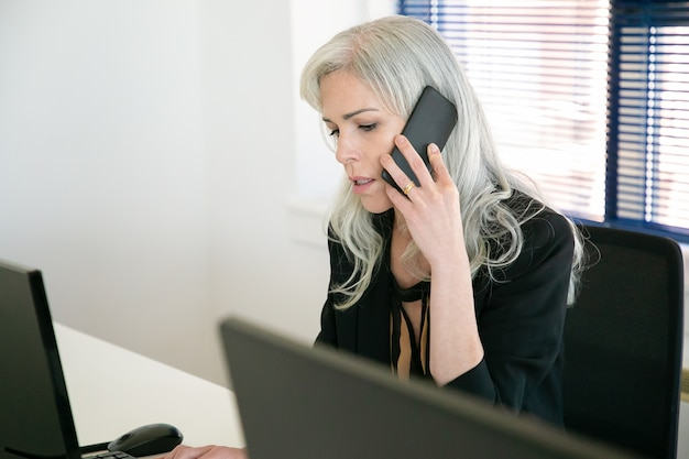 Kaukasische manager aan tafel zitten en praten via smartphone. mooie peinzende onderneemsters van middelbare leeftijd die in bureau werken en op monitor kijken. bedrijfs-, expressie- en bezettingsconcept
