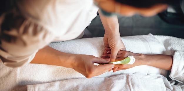 Kaukasische masseur die speciale crème toepast voordat de massagesessie in de spa-salon wordt gestart