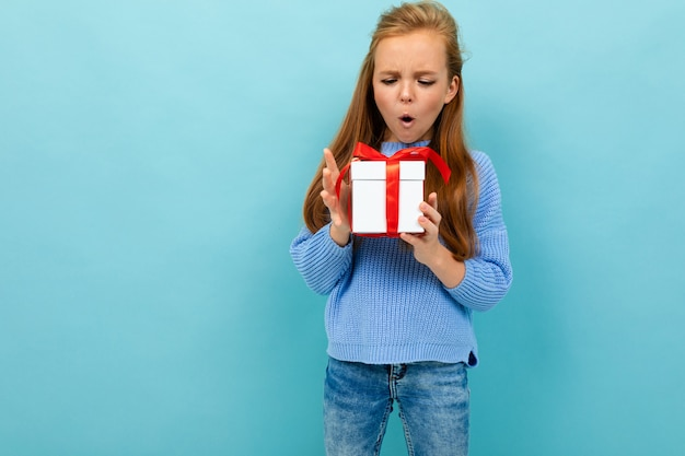Kaukasische meisje houdt een witte doos met cadeau en heeft veel emoties geïsoleerd op blauwe achtergrond